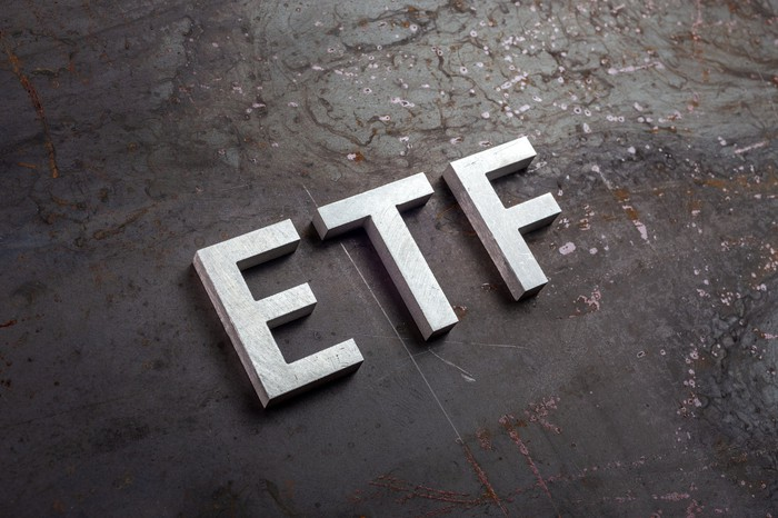 Big block letters lying on a brown surface that read ETF.