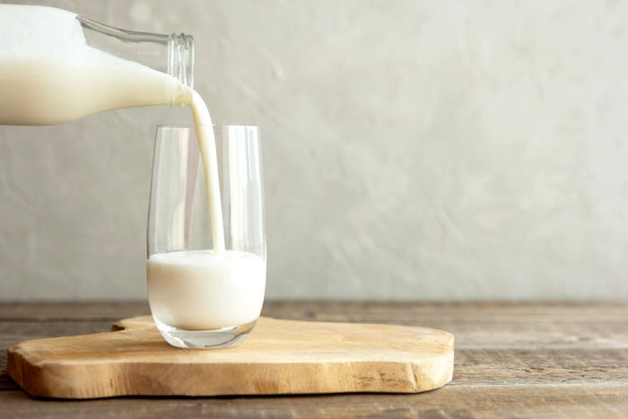 Milk being poured out of a glass bottle into a drinking glass.