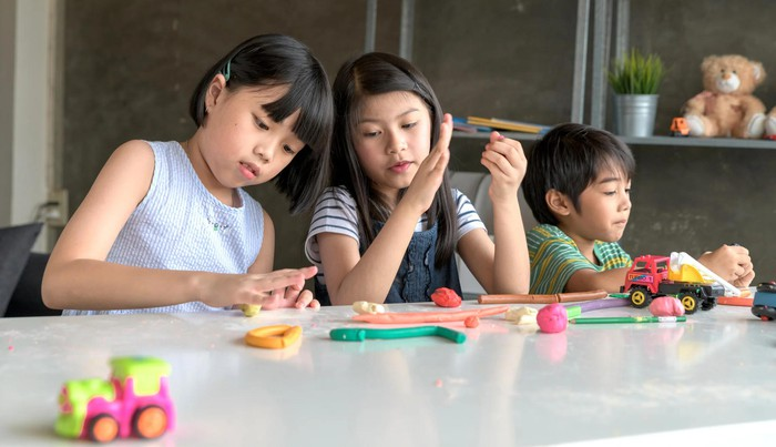 Three children playing with various toys at a table.