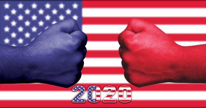 Two fists aiming at each other with one painted red for Republicans and the other painted blue for Democrats.
