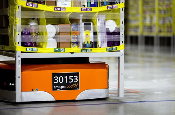 An Amazon Robotics robot drive unit moving a container of goods through a fulfillment center.