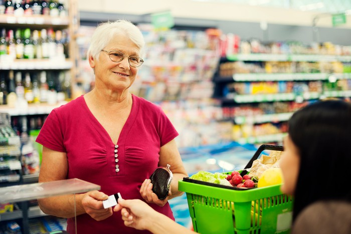 A senior woman buying groceries and handing a credit card to the cashier.