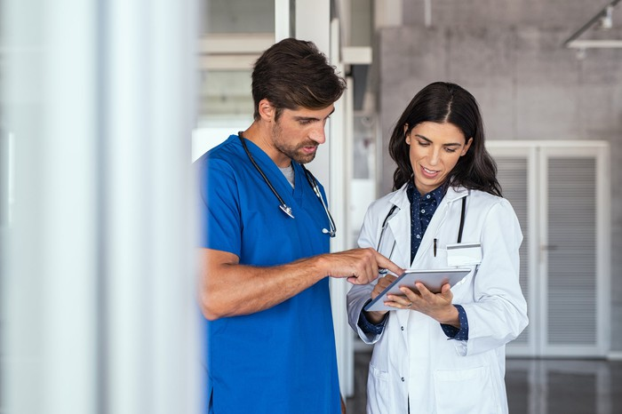 Two healthcare professionals looking at a chart.