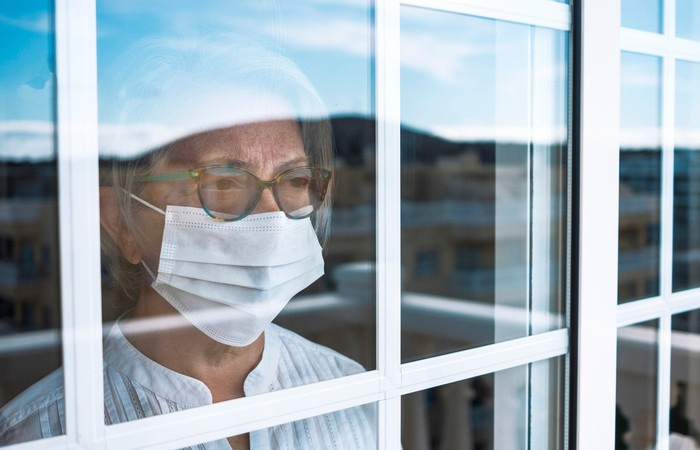 An elderly woman wearing glasses and a surgical mask looks out of a window.