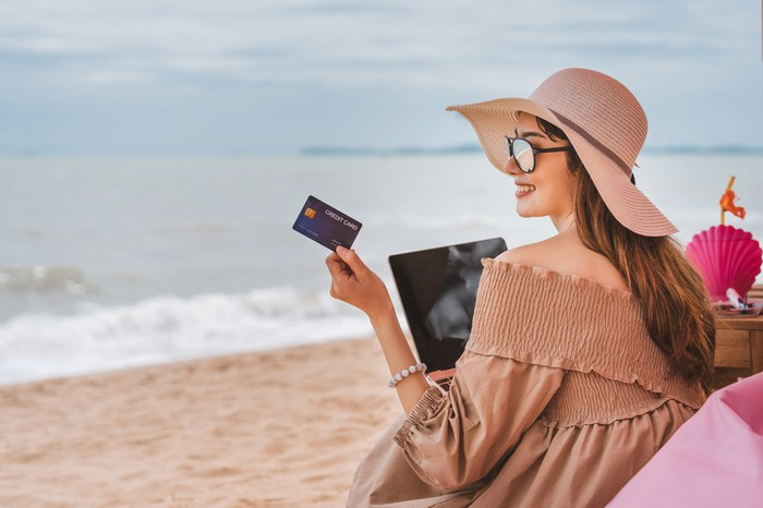 A young woman holds up a card while sitting on a beach with her laptop.