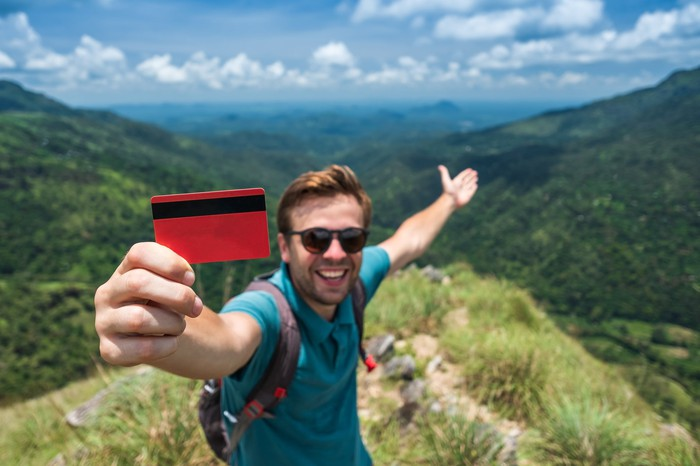 A young man on top of a mountain holds up a credit card.