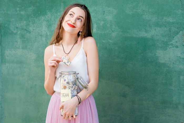 Smiling young woman holding jar of cash.