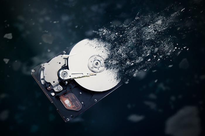 A hard disk drive shatters into pieces up and to the right.