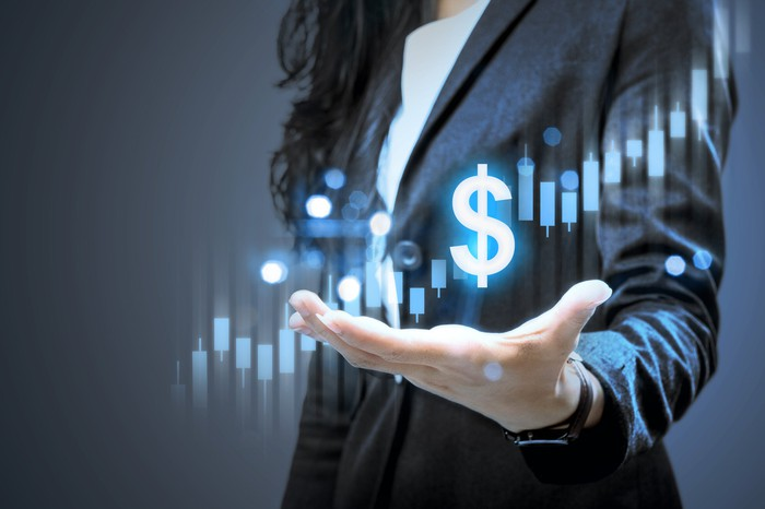 Woman holding hand out with images of an ascending stock chart and a dollar sign above her hand