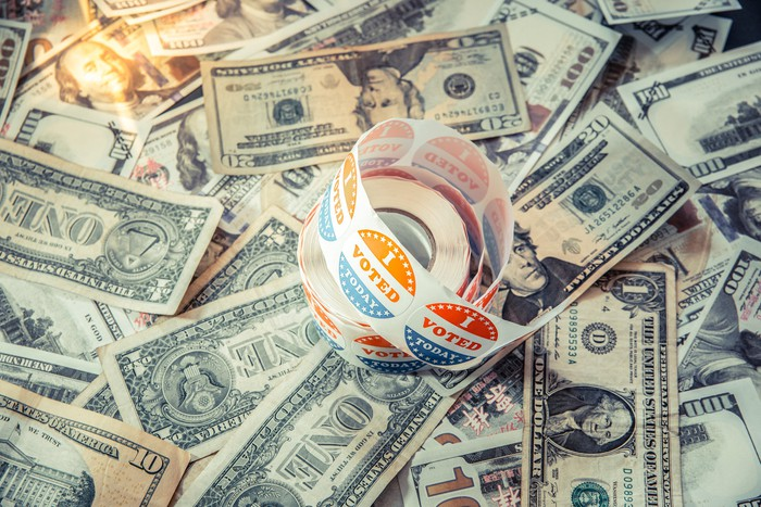 """A roll of """"I voted"""" stickers on top of a pile of cash."""