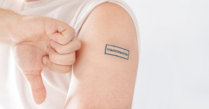 "Thumb down next to an arm with ""vaccinated"" stamped on it"