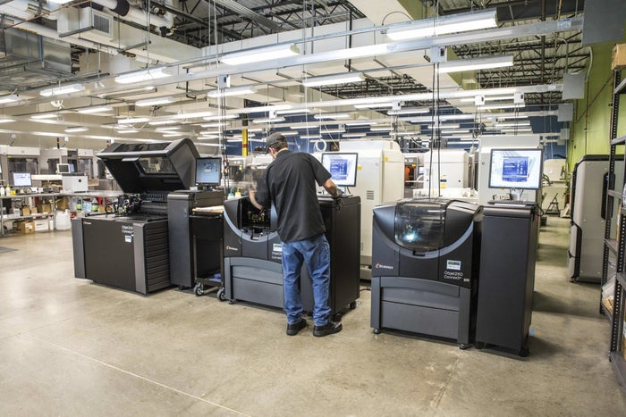 Male operator standing in front of a 3D printing machine in a company manufacturing facility.