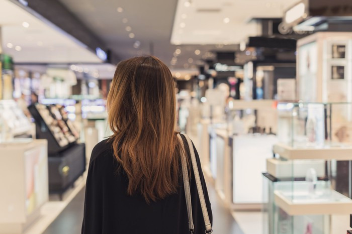 A woman walks through the cosmetics department in a department store,