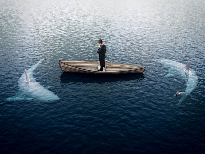 A man standing on a small boat with two sharks circling in the water.
