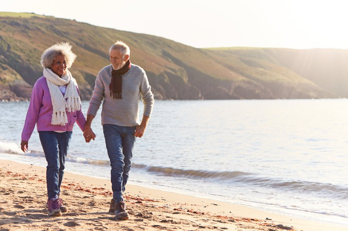 Older couple walking on the beach holding hands
