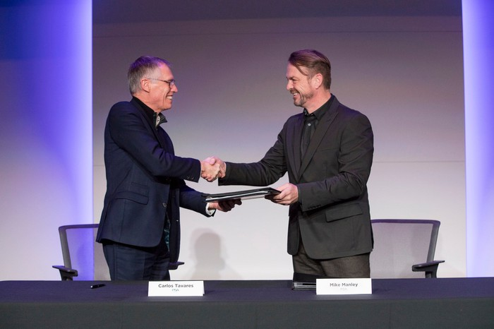 The two CEOs are shown shaking hands in front of a table.