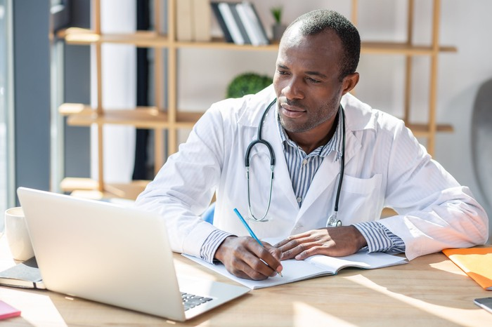 Male healthcare provider working on laptop with notebook and pen in his hands.