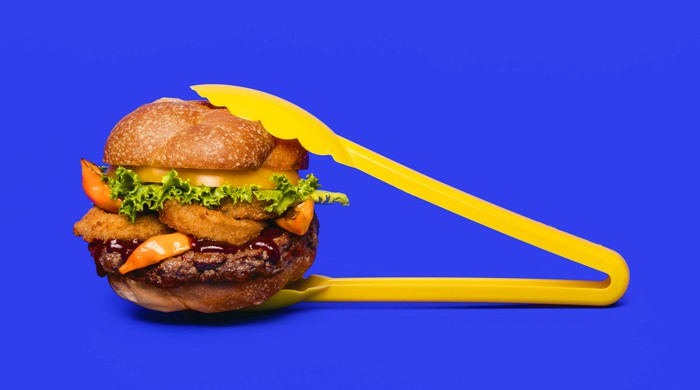 An Impossible Burger held in yellow plastic tongs, with a blue background.