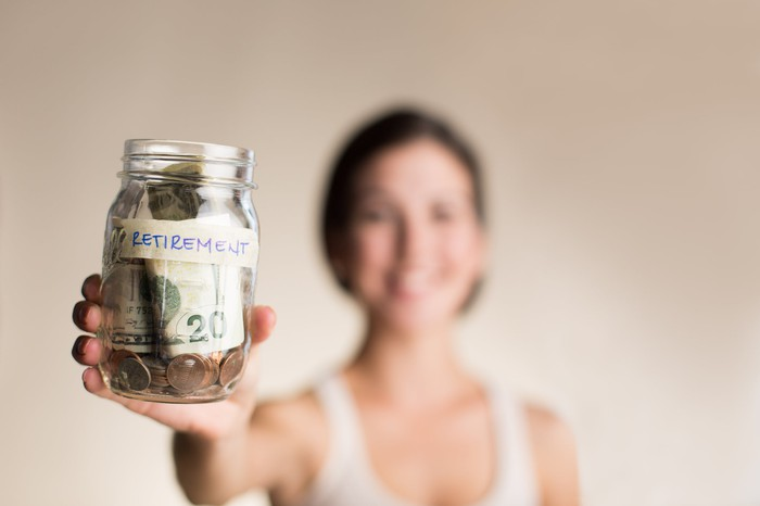 A woman holds her retirement savings in a jar.