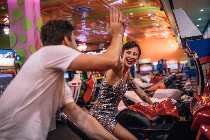 Man and woman high fiving at an arcade