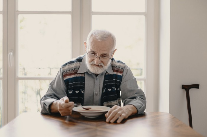 Older person at table holding a spoon over a bowl.