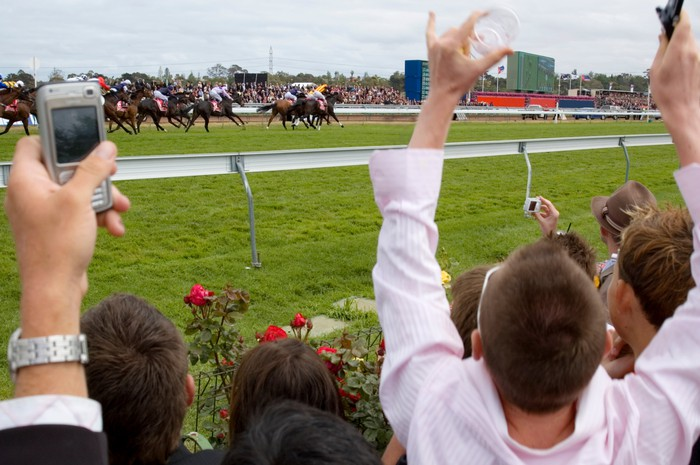 Spectators cheering at a horse race.