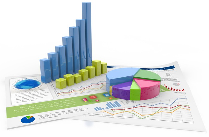 A collection of three-dimensional business charts lying on top of printed charts.