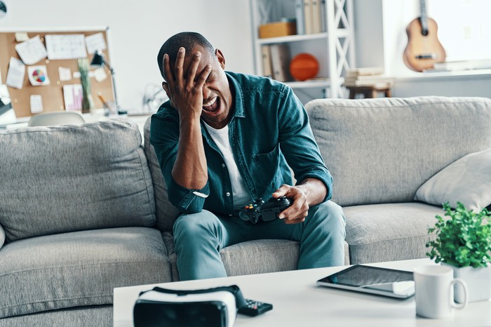 Man seated on couch, reacting to video game disappointment.