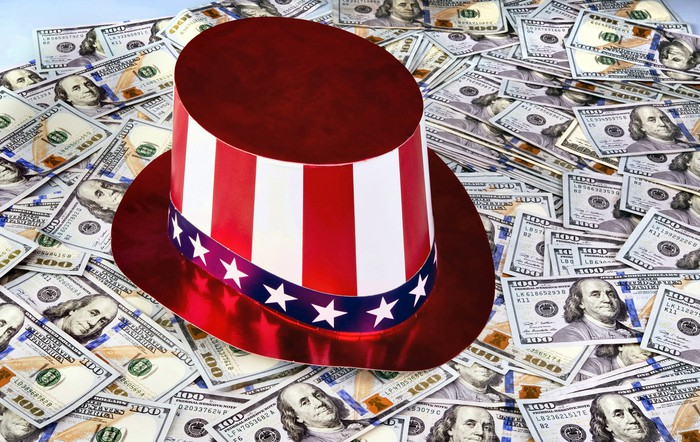 Hat with red, white, and blue stripes and stars sitting on many hundred dollar bills.