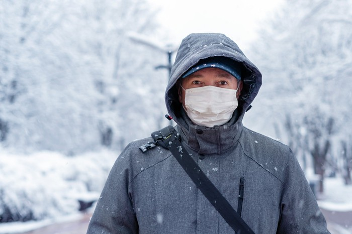 A man wearing a medical mask in a snowy background.