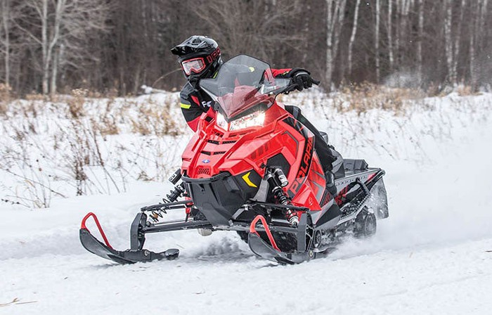 A snowmobile rider leans out to the right
