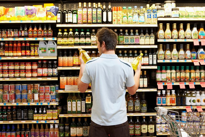 A man shopping the cooking oil section at a supermarket.