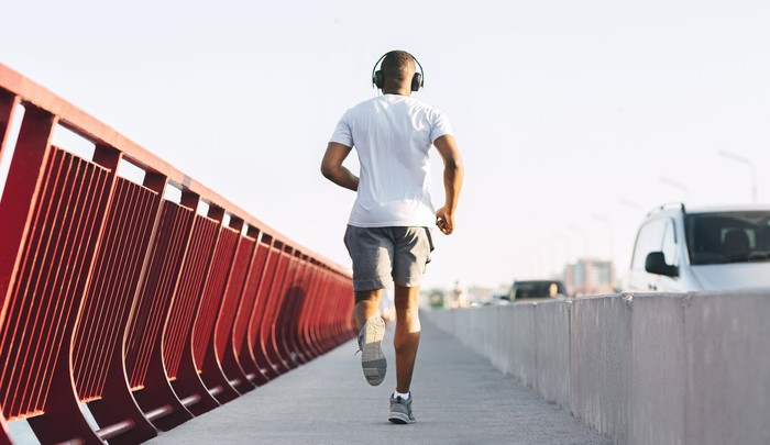 Man jogging along bridge with headphones