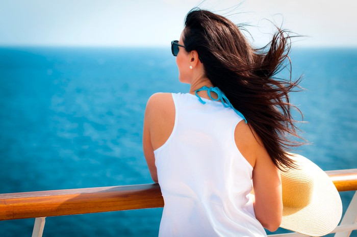A woman stands on a cruise ship deck and looks out to sea.