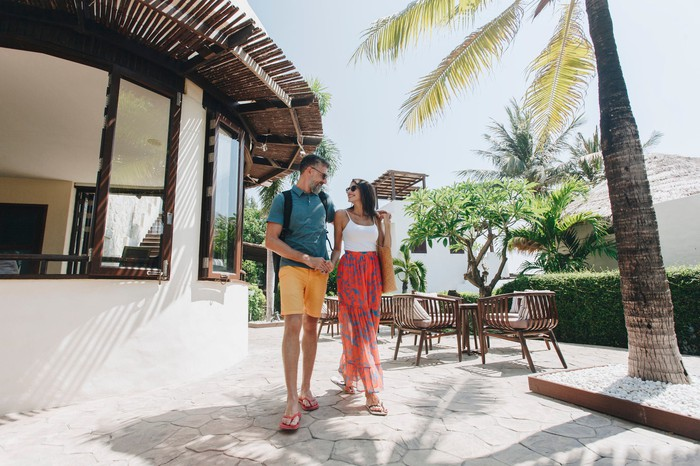 A man and a woman walking outside a tropical resort