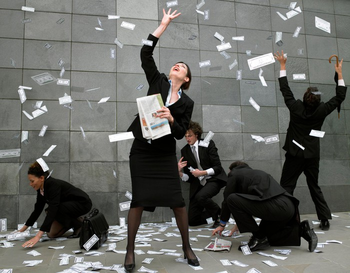 A group of smiling businessmen and women collect dollar bills falling from the sky.