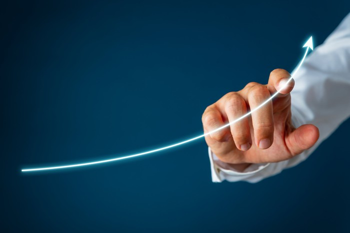 Finger pointing to lighted line sloping upward