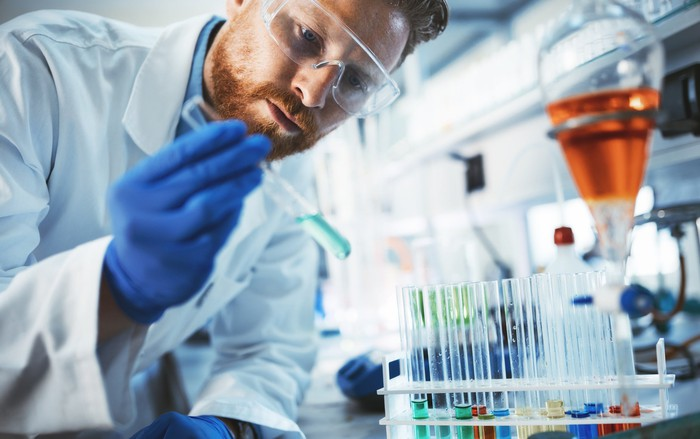Male scientist in lab holding a vial with solution in it.