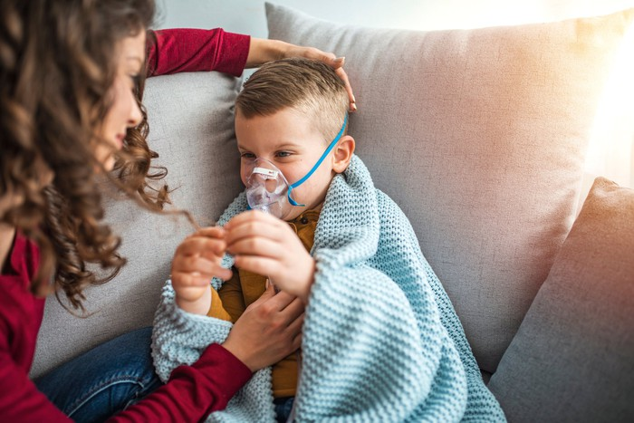 A child with cystic fibrosis gets an inhaler treatment.