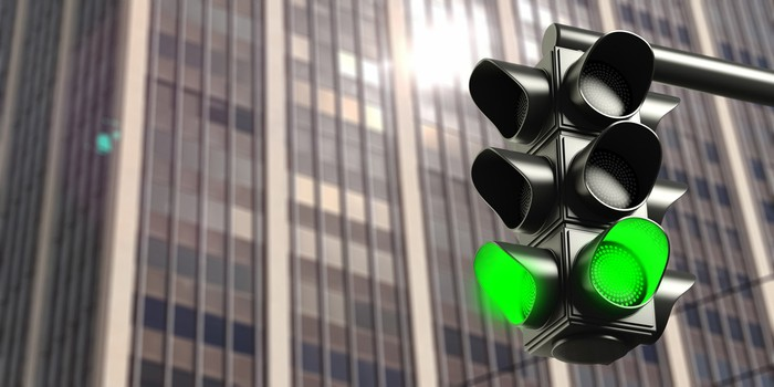 A green light in front of a modern office building, symbolizing regulatory approval.