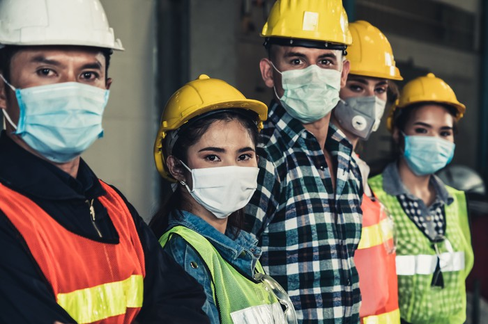 A line of 5 young men and women wearing hard hats, safety vests, and masks.