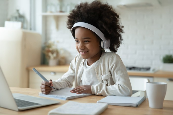 Middle school girl holding a pen and notebook, working on a laptop while wearing earphones