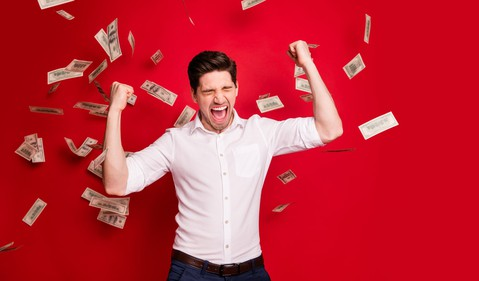 Man celebrating as $100 bills fall from above