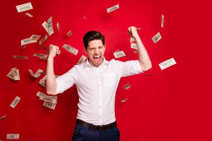 Man celebrating as $100 bills fall from above.