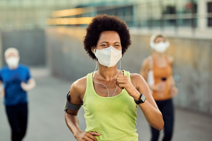Several people running while wearing face coverings.