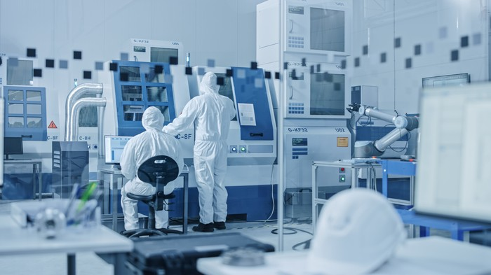 Two lab reachers dressed in protective gear face a large machine in a pharmaceutical lab colored mostly blue and white.
