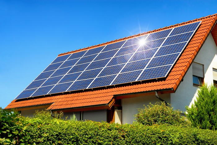 Home with large solar installation on the roof on a sunny day.
