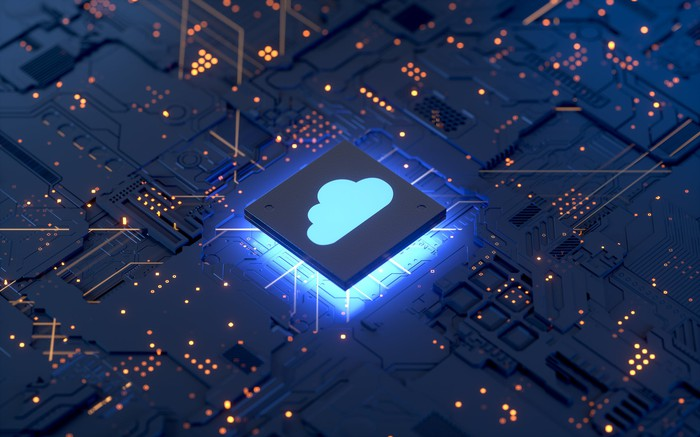 A computer chip with a glowing blue image of a cloud on top of it.