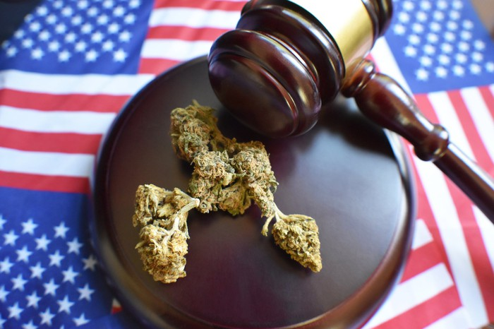 A bud of dried marijuana on a judge's gavel, with American flags in the background.