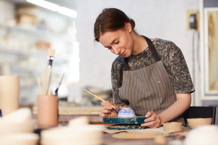A woman hand-painting pottery.